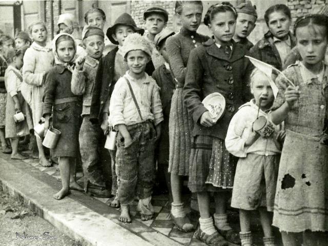 Fotografie datată 3 mai 1948, pe spatele căreia scrie, în engleză, o explicație tristă «Copii români așteptând la rând pentru a primi mâncare furnizată de Fondul Internațional de Urgență pentru Asistența Copiilor/ ONU»